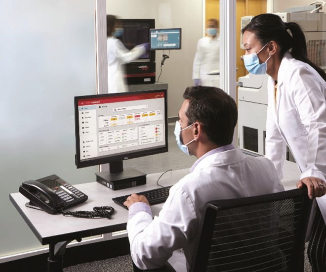 two people in lab coats looking at a computer